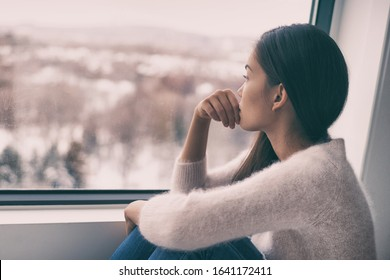 Sad pensive woman at home Winter depression - seasonal affective disorder mental health looking out the window alone. Self isolation - Shutterstock ID 1641172411