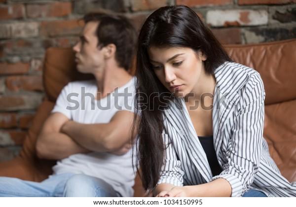 Traurige pensionierte junge Mädchen denken an Beziehungen Probleme auf Sofa sitzen mit beleidigtem Freund, Konflikte in der Ehe, verärgerte Paar nach Kampf Streit, die Entscheidung über das Scheitern zu treffen Scheidung