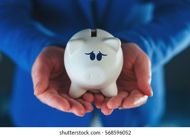 Sad piggy coin bank in businesswoman's hands, desperate look on face