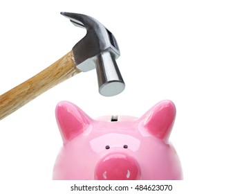 A sad pink piggy bank is about to be hit by a hammer in old vintage tone