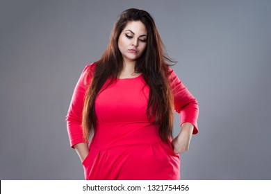 Sad plus size fashion model in red dress, fat woman on gray background, studio shot