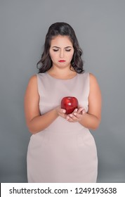 Sad plus size woman looking on apple on gray background. Diet concept