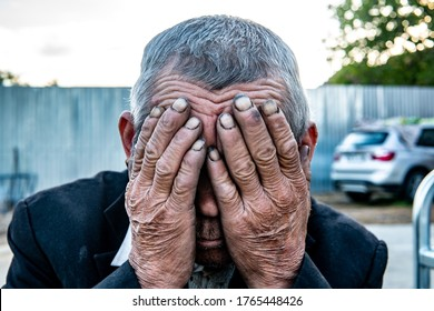 Sad and poor worker man covering his face. Concept of poverty