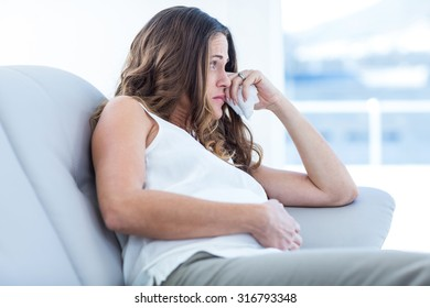 Sad pregnant woman sitting on sofa at home