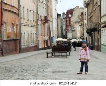 Sad preschooler girl staying alone among old street, she is lost, spring outdoor