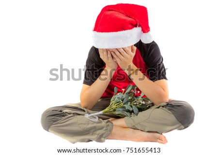 Sad pre-teen boy with mistletoe isolated on white background