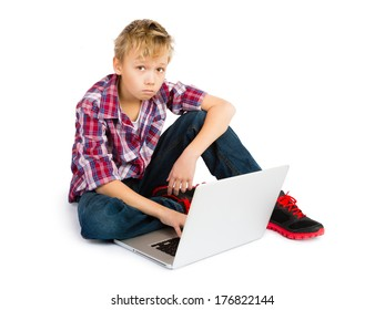 A sad pre-teen boy sitting with a laptop computer