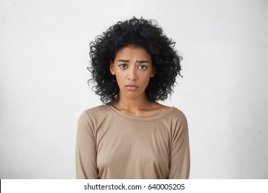 Sad pretty girl feeling upset while spending time at home alone. Beautiful young dark-skinned female with Afro hairstyle staring at camera with unhappy or regretful look against studio wall