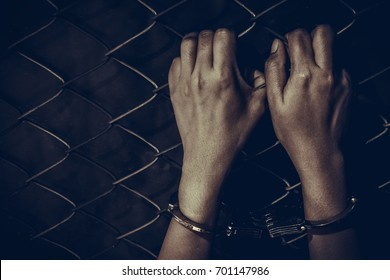 Sad prisoner woman with handcuffs holding rust metal fence with dark tone style