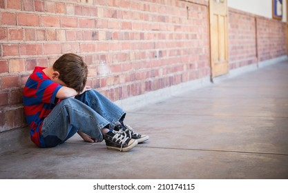 Sad pupil sitting alone in corridor at the elementary school