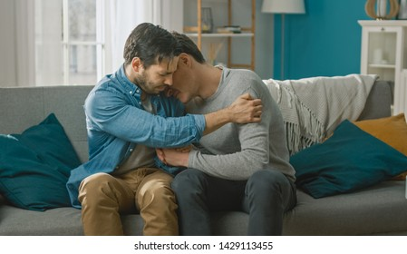 Sad Queer Drama Concept. Boyfriend is Unhappy and Depressed About Something. His Gay Friend is Comforting Him, Holding His Hands. Miserable Man Puts His Head on a Shoulder and Cries.