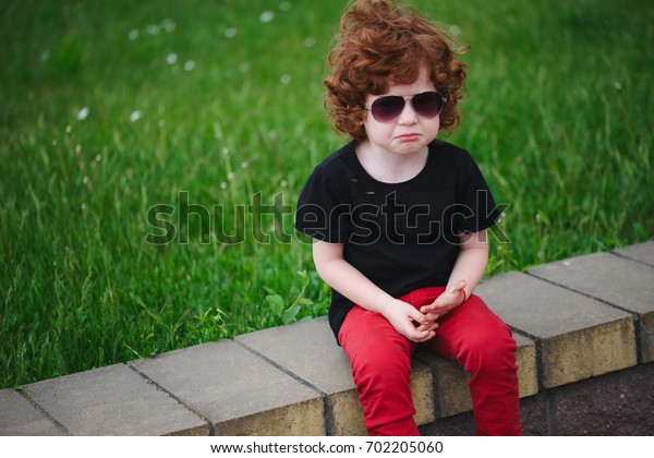 sad red haired boy in summer park