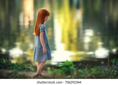 sad red-haired girl standing by the water