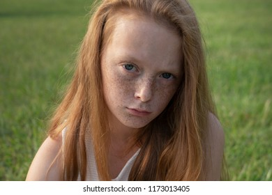 Sad red-haired little girl with freckles looking in camera with unhappy eyes