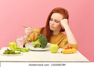 Sad red-haired woman in bad temper keeping strict vegetarian diet being tired of restrictions and hates greenery. Teenage girl holds broccoli on fork while making disgusting grimace