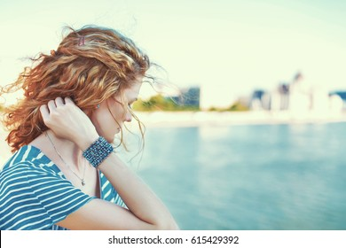 Sad redhead woman looking away over river outdoor
