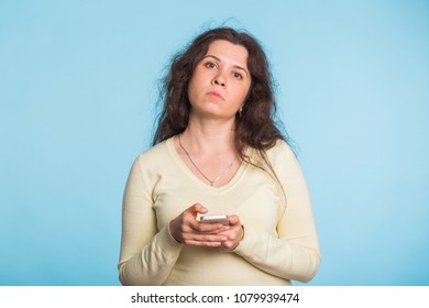 Sad and resentful woman waiting for excuses and explanations and is reproachfully looking isolated on blue background.
