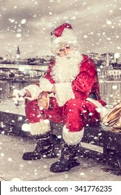 Sad Santa Claus with cigar and bottle of brandy outdoor