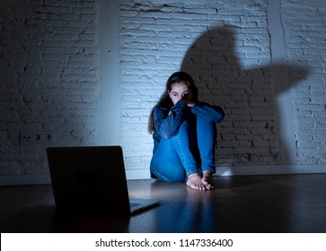 Sad and scared female Young woman with computer laptop suffering cyberbullying and harassment being online abused by stalker or gossip feeling desperate and humiliated in cyber bullying concept.