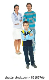 Sad schoolboy standing with arms crossed in front of smiling parents  in first day of school against white background