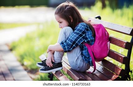 Sad schoolgirl sitting in the park. Education, lifestyle concept