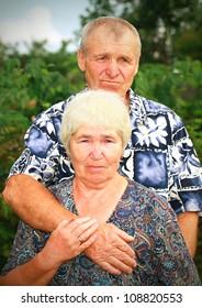 Sad senior couple embracing outdoors