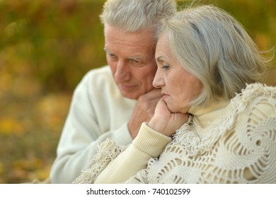 Sad senior couple in  park