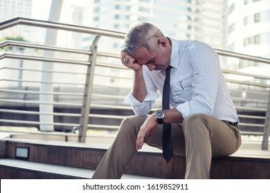 Sad senior gray hair businessman headache and look down with depress feeling due to positive COVID-19 disease. Business problems, Fired, Unemployed, bankrupt, work from home, quarantine, health care.