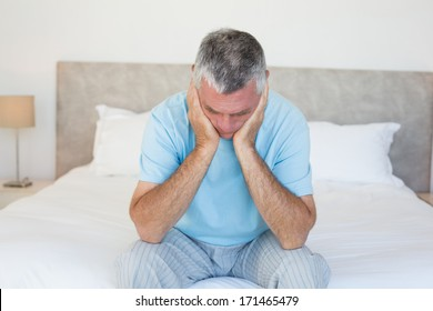 Sad senior man with head in hands sitting on bed at home