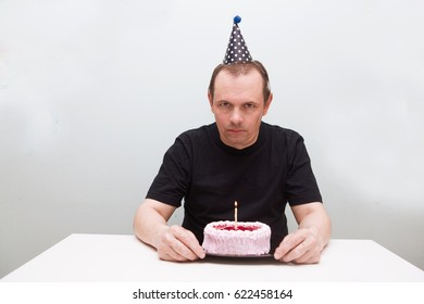 Sad senior man is sitting at a table with birthday cake