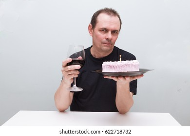 Sad senior man is sitting at a table with birthday cake and glass of wine