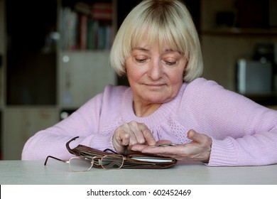 Sad senior woman, an elderly pensioner counting coins on her palm, wallet with money, eye-glasses at the table, concept of financial security in old age, indoor portrait, focus on the hand with coins