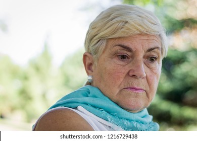 Sad senior woman with green shawl looking down at park. Depressed elder blonde lady. Sleeveless white shirt, thoughtful, pensive expression