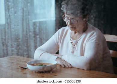 Sad, senior woman having lack of appetite