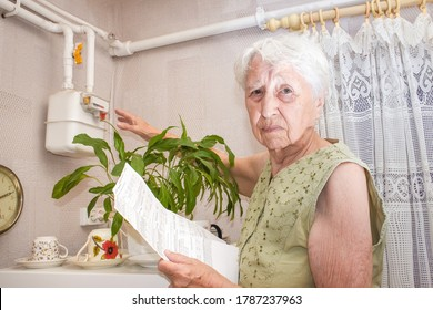 The sad senior woman at home and examines gas bill. She is under stress when checking accounts.