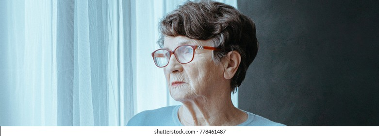 Sad senior woman looking through the window waiting for a visit from her family, feeling lost and lonely