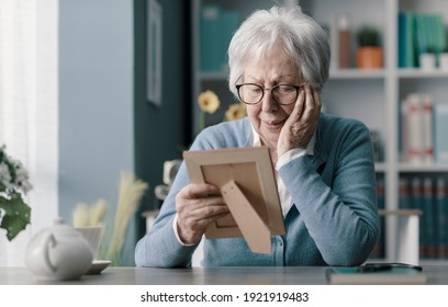 Sad senior woman mourning the loss of her husband, she is holding a picture and crying
