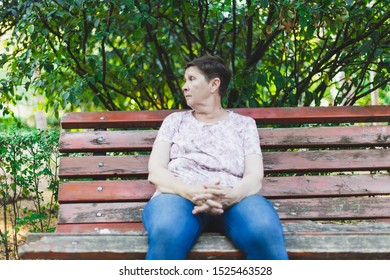 Sad senior woman sitting alone on a bench while looking in the distance - Depressed and confused cute old lady with short brown hair feeling lonely in the park