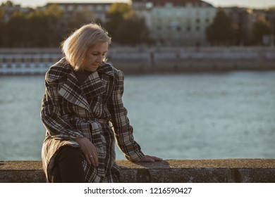 Sad senior woman sitting by the river alone.Toned image.