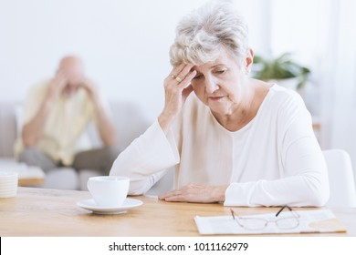 Sad senior woman sitting at a table after a quarrel with her husband