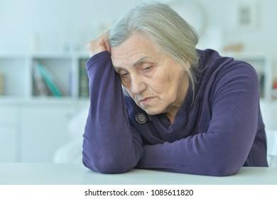 sad  senior woman sitting at table