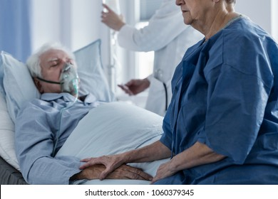 Sad senior woman supporting her terminally ill husband lying in the hospital