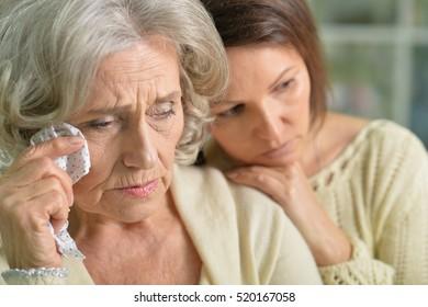 Sad senior and young women