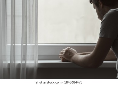 Sad serious adult man sitting at window in home. Thinking about life. Back view. Dark gloomy atmosphere.