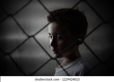 Sad serious boy behind a chain link fence