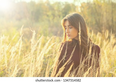 sad serious young woman in dry autumn grass