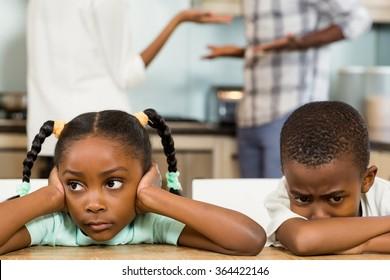 Sad siblings against parents arguing in kitchen