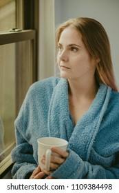 Sad sick woman by a window with a bathrobe holding a mug of tea or coffee