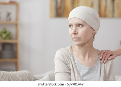 Sad sick woman with lung cancer sitting at home with friend