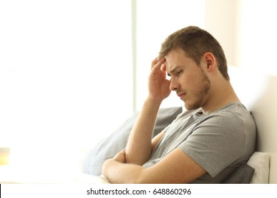 Sad single man lamenting sitting on the bed on the bed of an hotel room or home